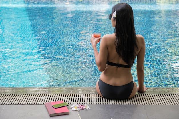 De vrouw drinkt sap dichtbij pool bij de zomer