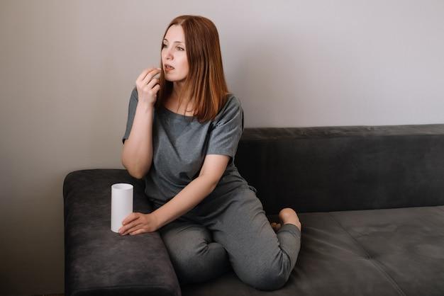 De vrouw drinkt thuis een zitting van de vitaminepil op een laag in de woonkamer