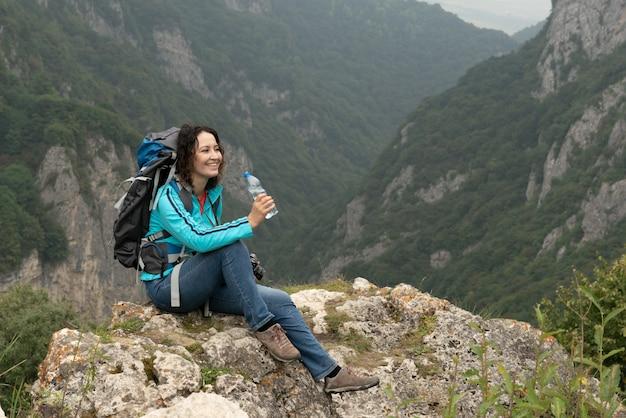 De vrouw drinkt water in de bergen.