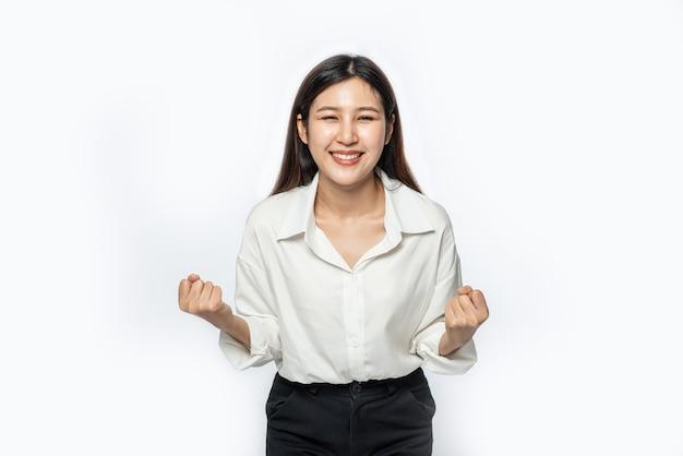 De vrouw droeg een wit overhemd en een donkere broek en maakte een grappige pose