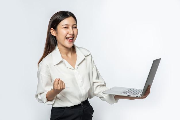 De vrouw droeg een wit overhemd en een donkere broek, hield een laptop vast en deed alsof ze vrolijk was