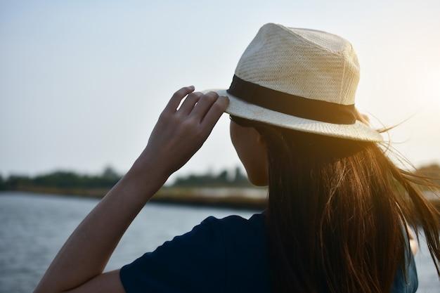 De vrouw droeg een wit t-shirt en een hoed, staande op de rivier en de twee handen aan de hemel.