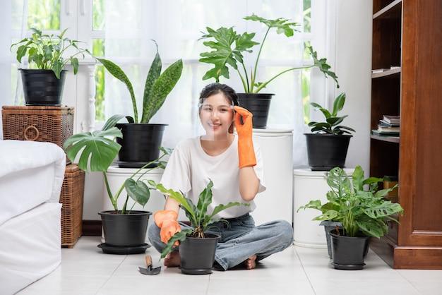 De vrouw droeg oranje handschoenen en plantte bomen in huis.