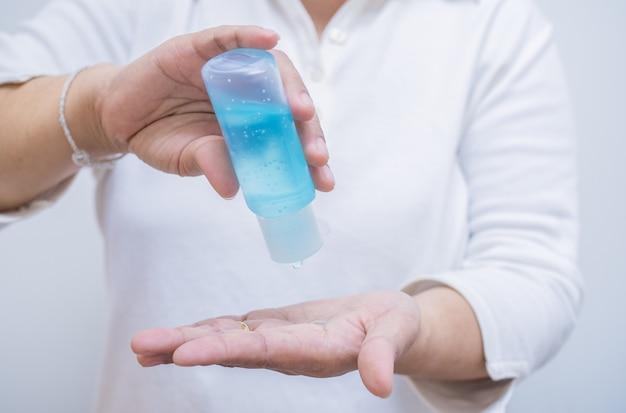 De vrouw drukt met de hand alcoholgel uit een pompfles om de handen te reinigen en coronavirusinfectie te voorkomen, initiële zelfzorg tijdens een epidemische crisis.