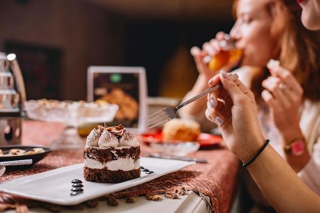 De vrouw eet geportioneerde cacaocake met witte room en chocoladestukjes