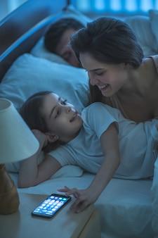 De vrouw en een klein meisje bellen in het bed. nachttijd