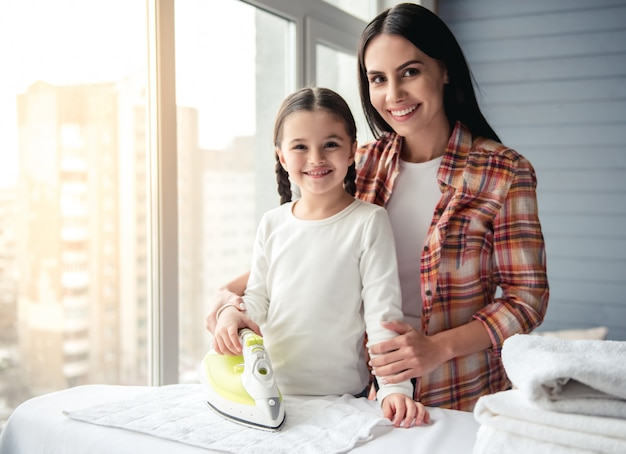 De vrouw en haar dochter glimlachen terwijl het strijken van linnen.