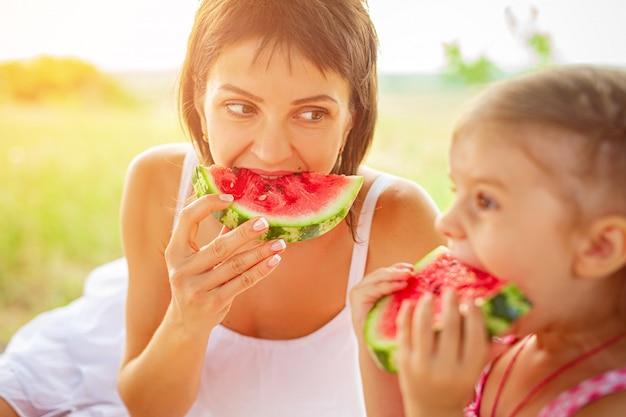 De vrouw en het meisje eten in openlucht plak van watermeloen op weide. moeder en dochter brengen samen tijd door. dieet, vitamines, gezond voedselconcept