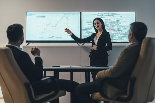 De vrouw en twee mannen bespreken in de buurt van een scherm in een kantoor