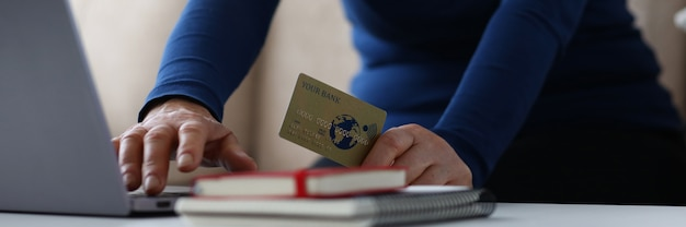 De vrouw gaat creditcarddetails in browser in laptop close-up