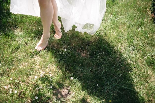 De vrouw gaat op blote voeten op het gras