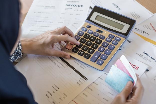 De vrouw gebruikt calculator om rekeningen in huisbureau te berekenen.