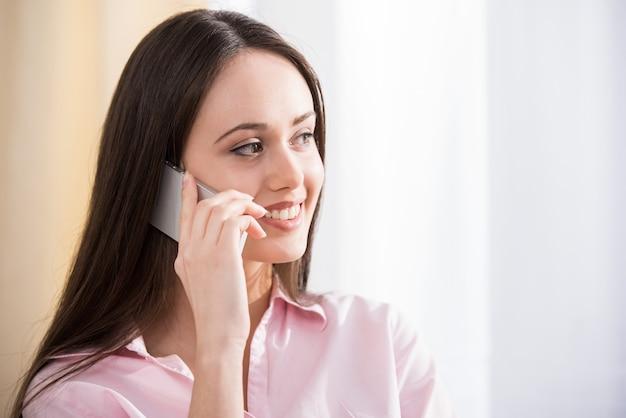 De vrouw gebruikt cellphone terwijl thuis het zitten op laag
