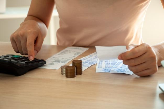 De vrouw gebruikt een calculator om uitgaven met rekeningen te berekenen die op de lijst worden geplaatst