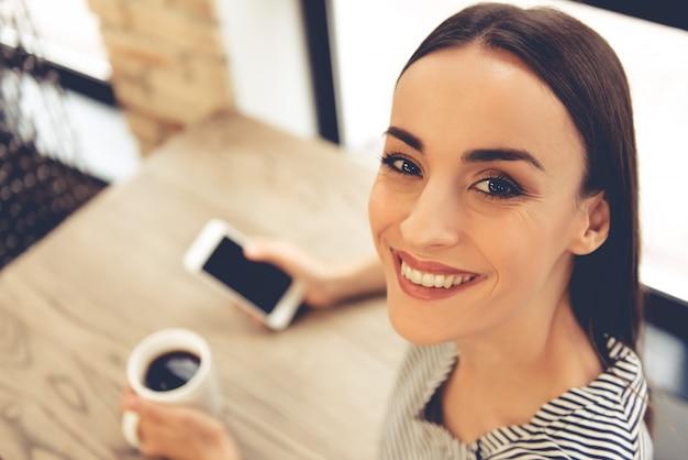 De vrouw gebruikt een smartphone en drinkt koffie