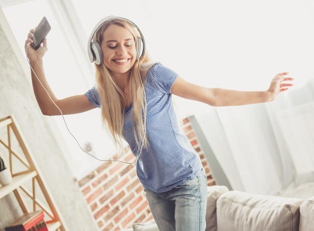De vrouw gebruikt een smartphone, glimlacht en danst thuis