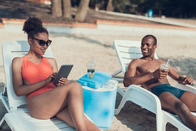De vrouw gebruikt tabletpc terwijl het drinken van de mens cocktail