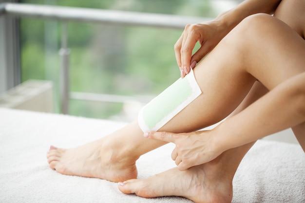 De vrouw gebruikt wasband om haar op benen te verwijderen