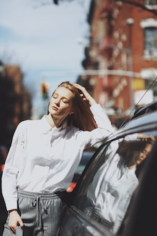 De vrouw geniet van de zonneschijn die aan een auto op de straat leunt