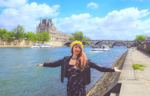 De vrouw geniet van haar vakantie in parijs met pont neuf op de rug, parijs, frankrijk.