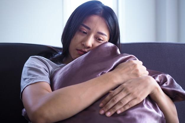 De vrouw ging zitten en omhelsde het kussen op de bank in huis. de uitdrukking en wanhoop en wanhoop.