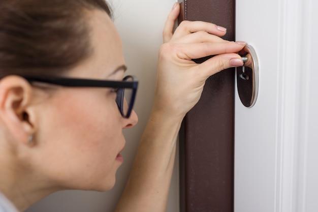De vrouw gluurt naar het sleutelgat, thuis in de voordeur