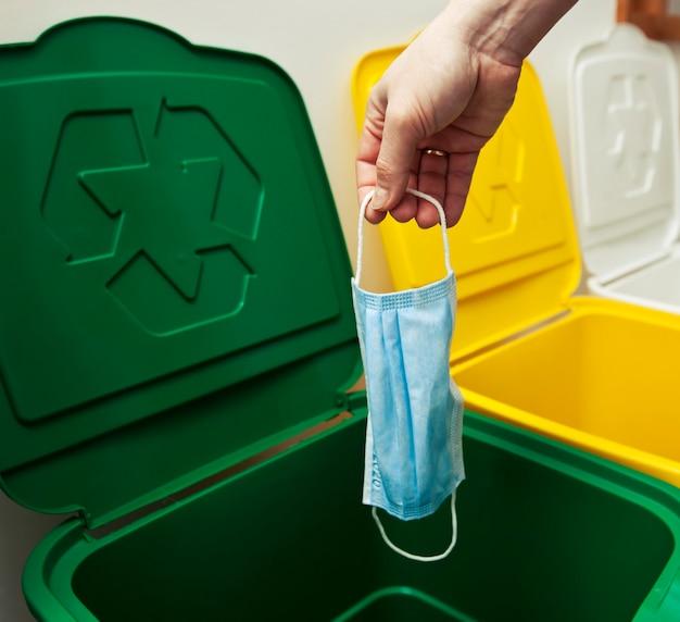 De vrouw gooit het medische masker in een van de drie vuilnisbakken