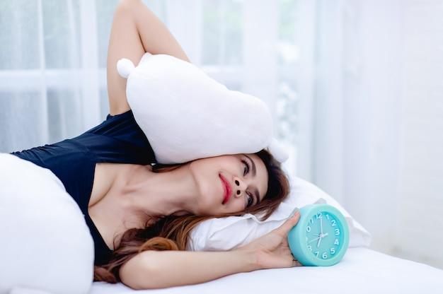 De vrouw haalde het kussen van het oor terwijl de wekker 's morgens klonk. het idee om wakker te worden om op tijd aan het werk te gaan