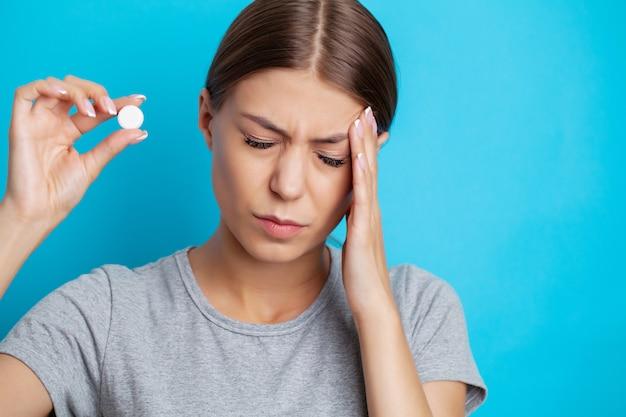 De vrouw heeft keelpijn en houdt een pil vast voor behandeling