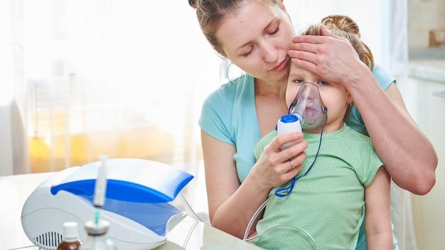 De vrouw helpt door het masker naar het kind te ademen