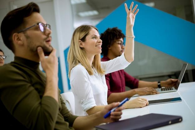 De vrouw hief omhoog haar hand voor vraag in conferentievergadering op