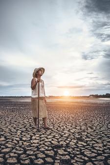 De vrouw hield zijn hand op en ving een siem op droge grond en keek naar de lucht.