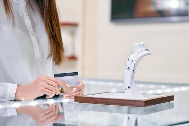 De vrouw houdt creditcard in haar handen en bevindt zich dichtbij de halsband in een juwelenwinkel