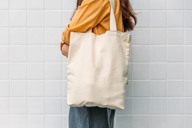 De vrouw houdt de stof van het zakcanvas