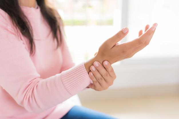 De vrouw houdt de verwonding van de polshand en het voelen van pijn, gezondheidsconcept.