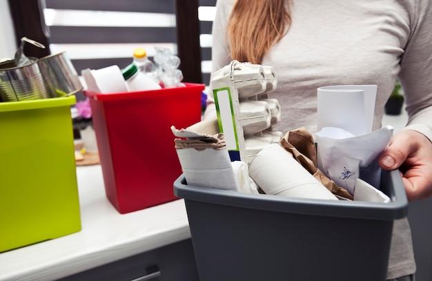 De vrouw houdt de volle plastic doos met papierafval vast