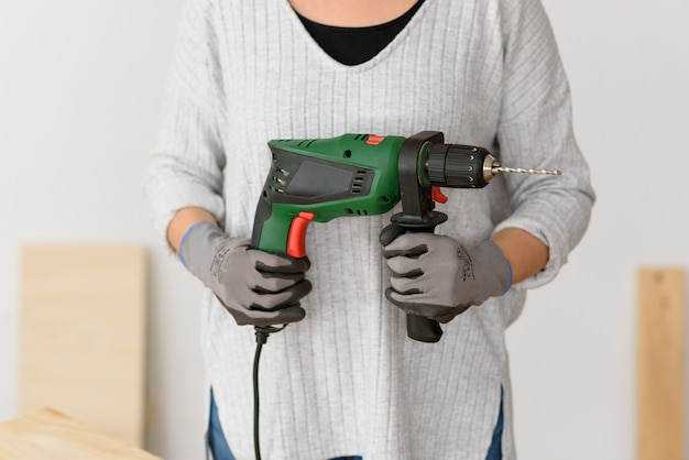 De vrouw houdt een boor in haar handen klaar om huisverbeteringen aan te brengen