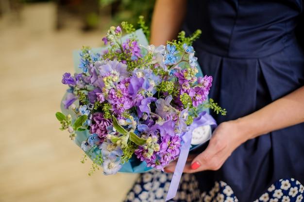 De vrouw houdt een mooie bloemsamenstelling