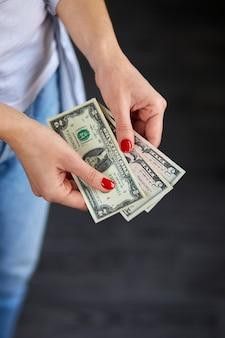 De vrouw houdt gelddollars in hand. concept van succes