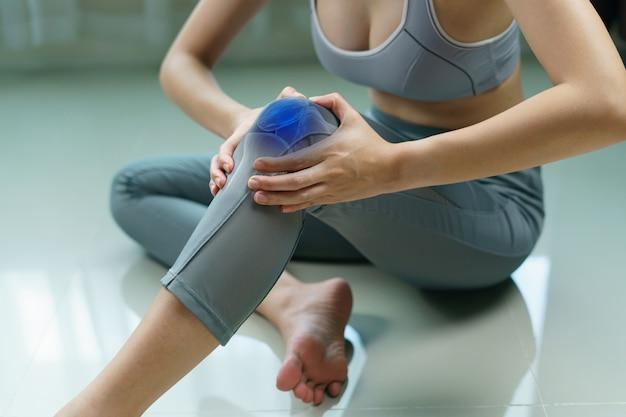 De vrouw houdt haar handen aan de knie, pijn in de knie benadrukt in blauw, geneeskunde, massageconcept.
