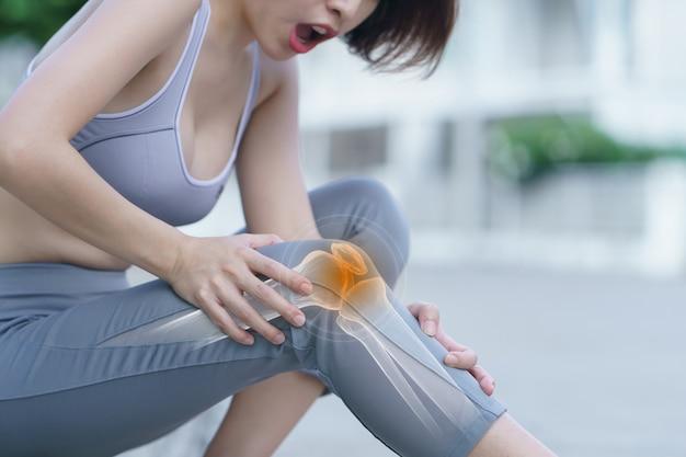 De vrouw houdt haar handen aan de knie, pijn in de knie benadrukt in rood, geneeskunde, massageconcept.