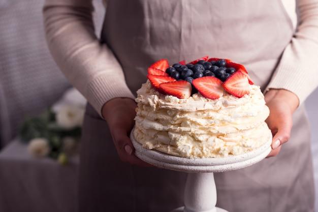 De vrouw houdt in haar handen beroemde cake van aardbeipavlova