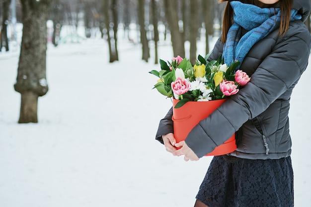 De vrouw houdt in haar handen rode geschenkdoos met prachtige boeket bloemen als een geschenk voor valentijnsdag