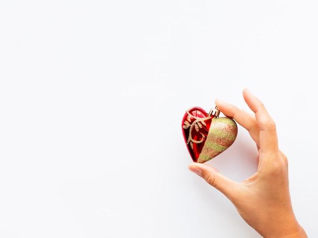De vrouw houdt nieuwjaardecoratie - rood hart op witte achtergrond