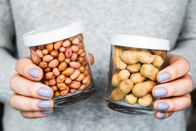 De vrouw houdt twee potten in haar handen - met pinda's in de schaal en geschilde pinda's