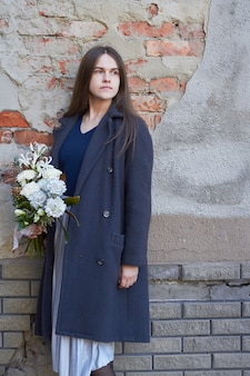 De vrouw houdt wit gestemd boeket tegenover bakstenen muur