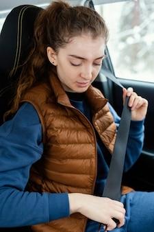 De vrouw in auto maakt veiligheidsgordel vast