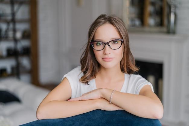 De vrouw in bril, houdt handen op rug van bank, stelt thuis in woonkamer.