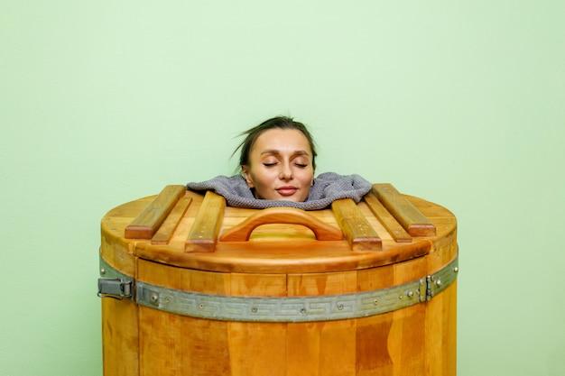 De vrouw in cedar spa vatlichaamsverjonging en ontspant sauna