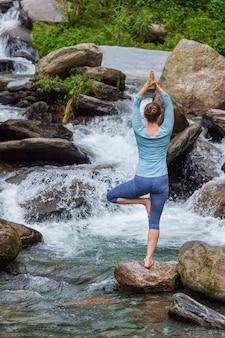 De vrouw in de boom van vrikshasana van yogaasana stelt in openlucht bij waterval